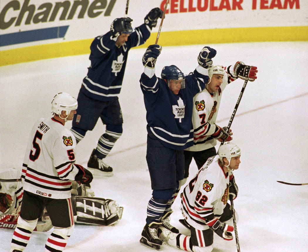 Toronto Maple Leafs' Mats Sundin celebrates over Chicago Blackhawks' Chris Chelios (7) and Bernie Nicholls after Dave Andreychuk's first period goal, Friday, May 19, 1995, in Game 7 of the Western ...
