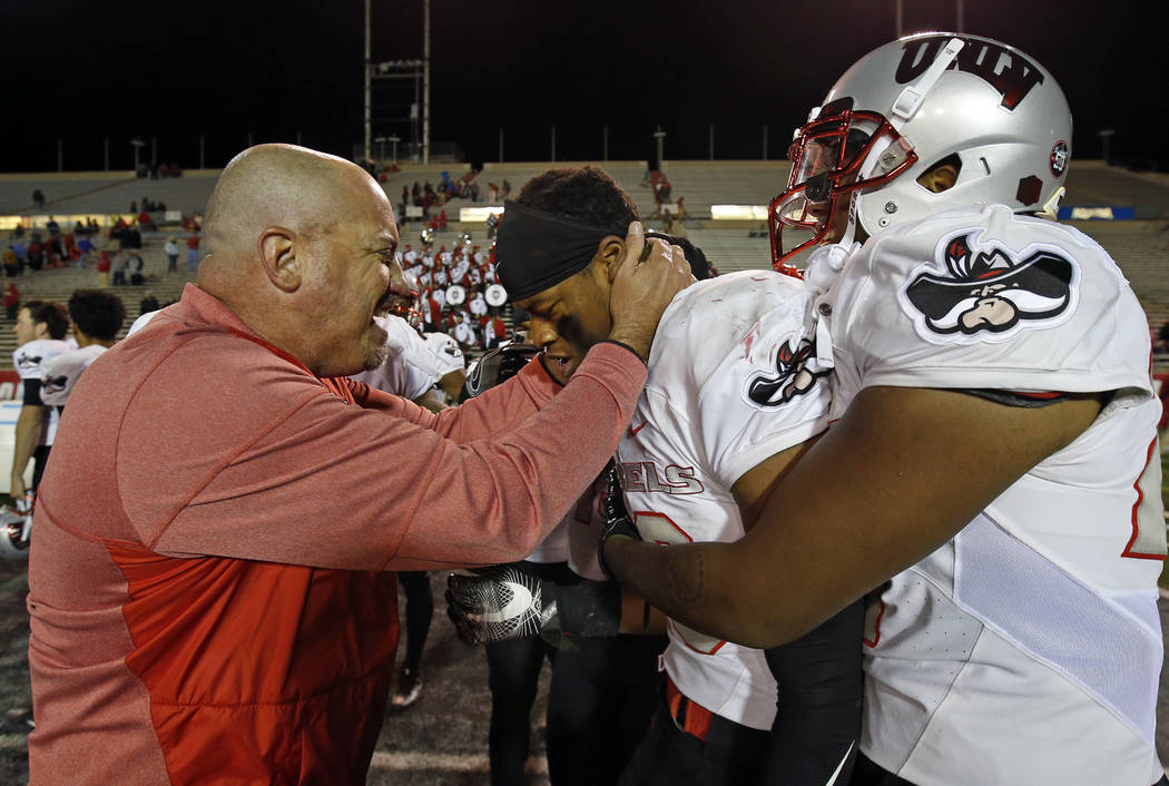 UNLV coach Tony Sanchez, left, congratulates linebacker Javin White (16) after White broke up a pass intended for New Mexico wide receiver Q' Drennan in the final minute of an NCAA college footbal ...