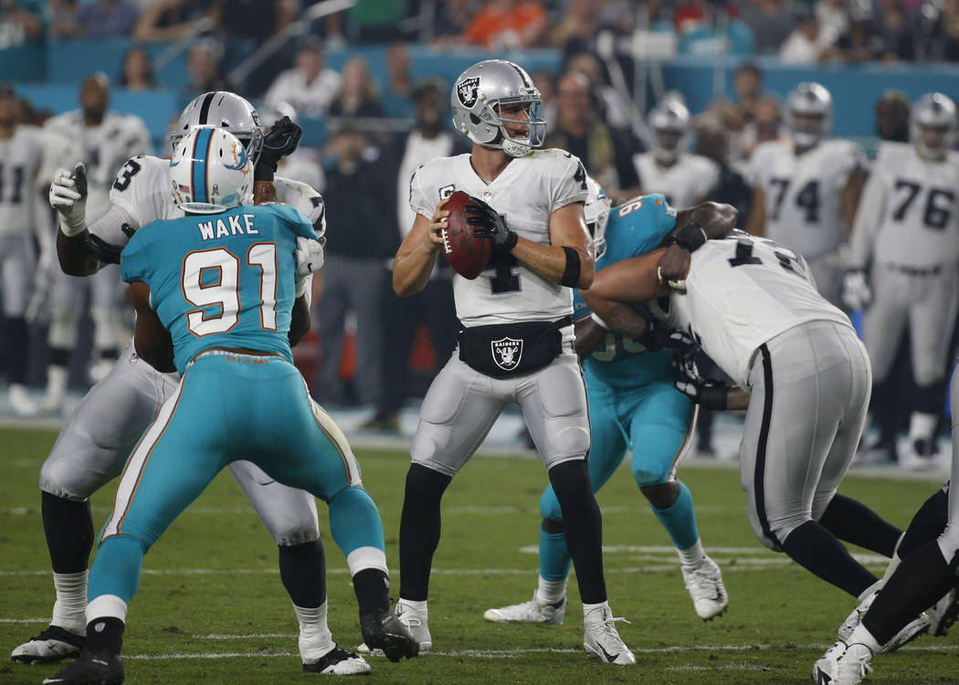 Oakland Raiders quarterback Derek Carr (4) looks to pass, during the first half of an NFL football game against the Miami Dolphins, Sunday, Nov. 5, 2017, in Miami Gardens, Fla. (AP Photo/Wilfredo Lee)