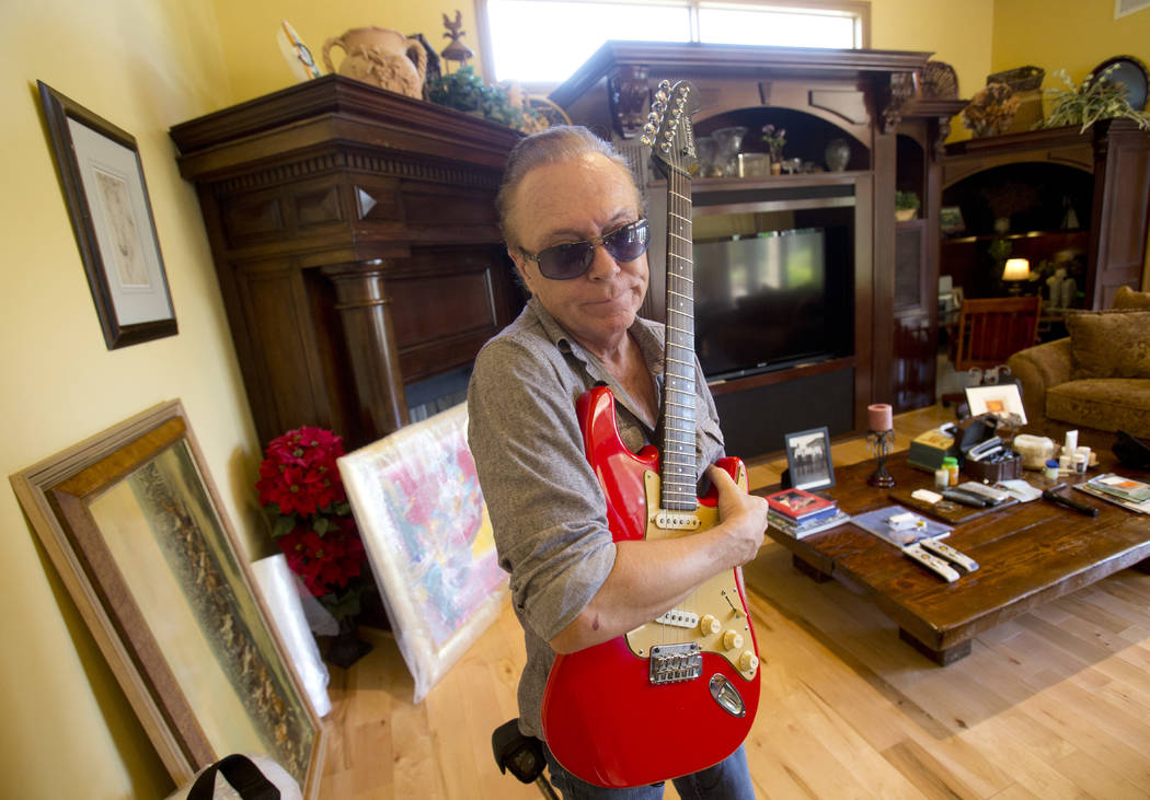 In this, Wednesday, July 22, 2015 photo, 1970s heartthrob David Cassidy holds one of his favorite guitars as he gives a tour of his five-bedroom Florida mansion in Fort Lauderdale, Fla. Cassidy di ...