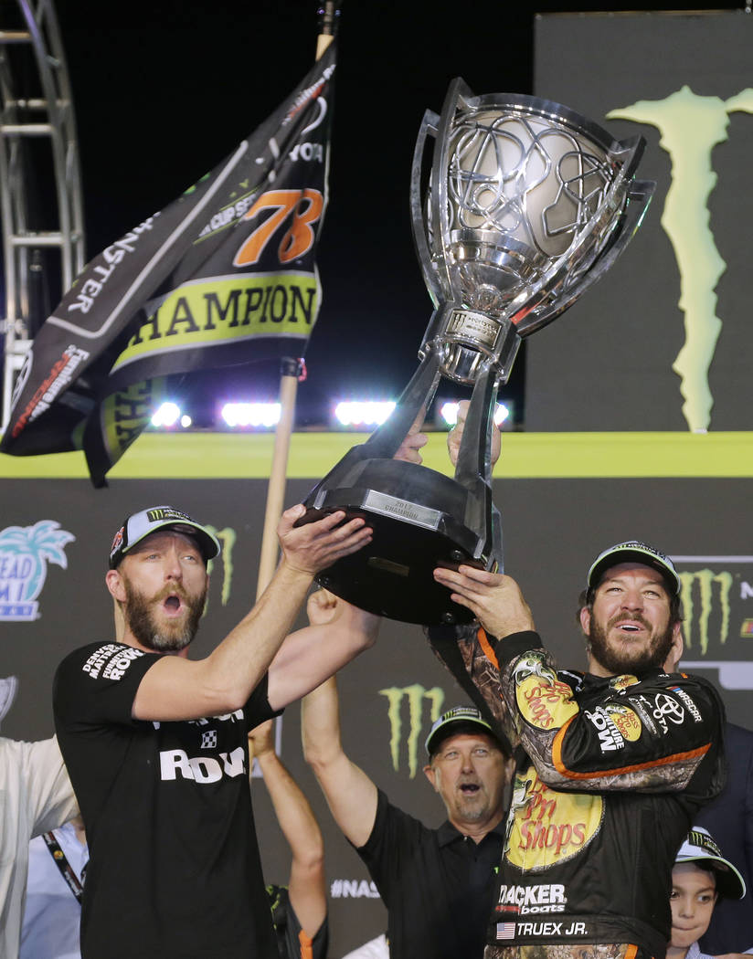Martin Truex Jr., right, and crew chief Cole Pearn celebrate in Victory Lane after winning the NASCAR Cup Series auto race and season championship at Homestead-Miami Speedway in Homestead, Fla., S ...