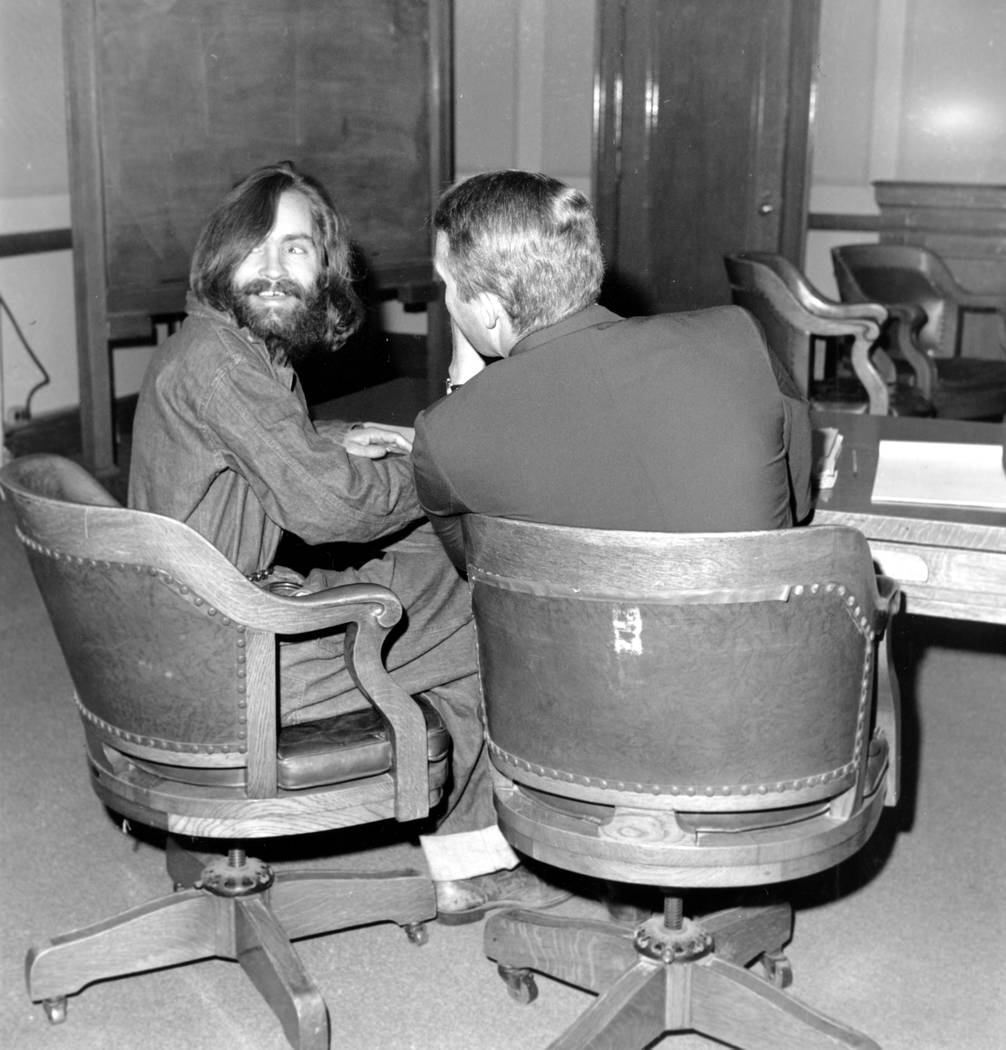Cult leader Charles Manson looks back and smiles as his attorney, public defender Fred Schaefer, talks to him in Independence, Calif., on Dec. 4, 1969.  Manson and his followers are charged with e ...
