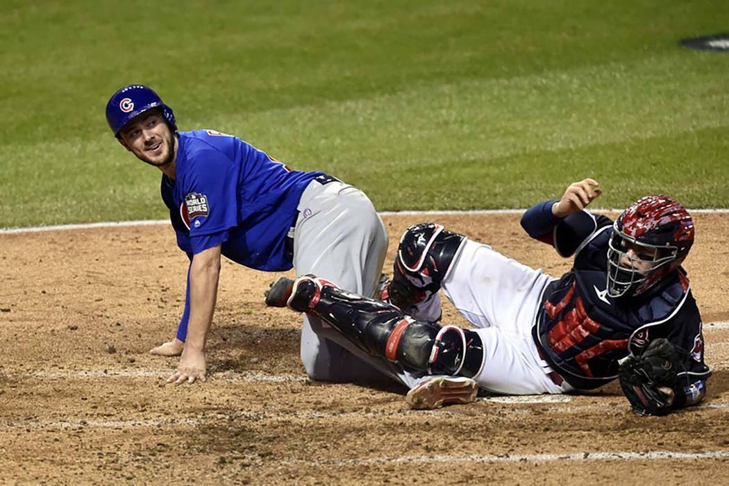 Chicago Cubs third baseman Kris Bryant (17) scores a run past Cleveland Indians catcher Roberto Perez (55) in the fourth inning in game seven of the 2016 World Series at Progressive Field in Cleve ...