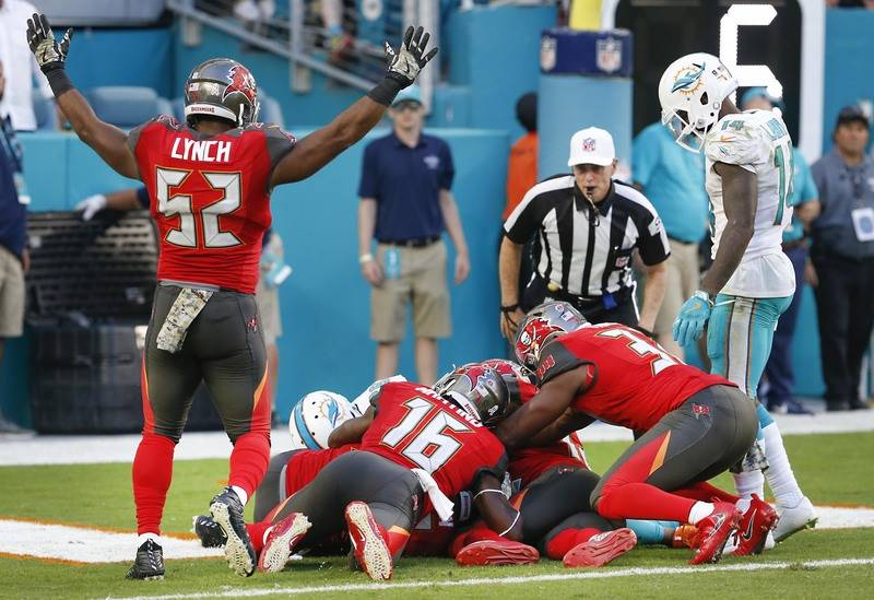 The Tampa Bay Buccaneers fall on a fumbled ball in the end zone for a touchdown during the second half against the Miami Dolphins at Hard Rock Stadium in Miami Gardens, Florida, Nov. 19, 2017. ( R ...