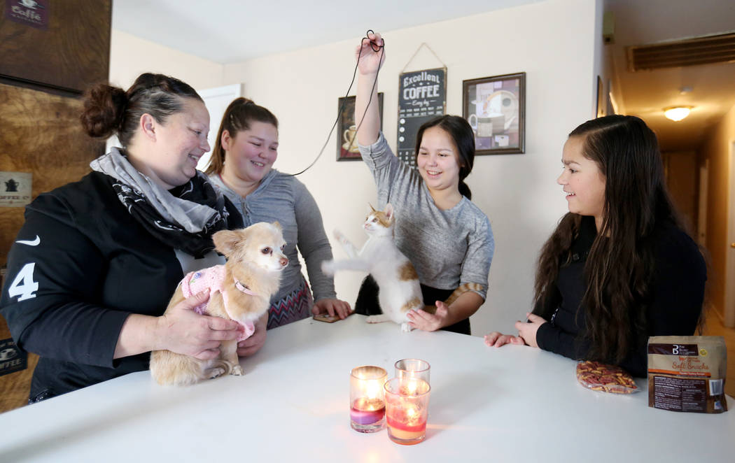 Elena Saccapilltio, left, holds her dog while her daughters Jazmen Segars, 19, left, Kalena Segars, 15, center, and Rozlyn Segars, 13, play with their kitten in their home in Las Vegas on Tuesday, ...