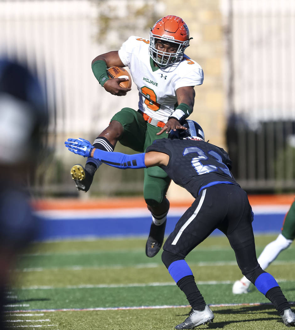 Mojave's Tawee Walker (3) jumps to avoid a tackle from Desert Pines' Andrew Williams (23) during the NIAA Class 3A state championship game at Bishop Gorman High School in Las Vegas on Saturday, No ...