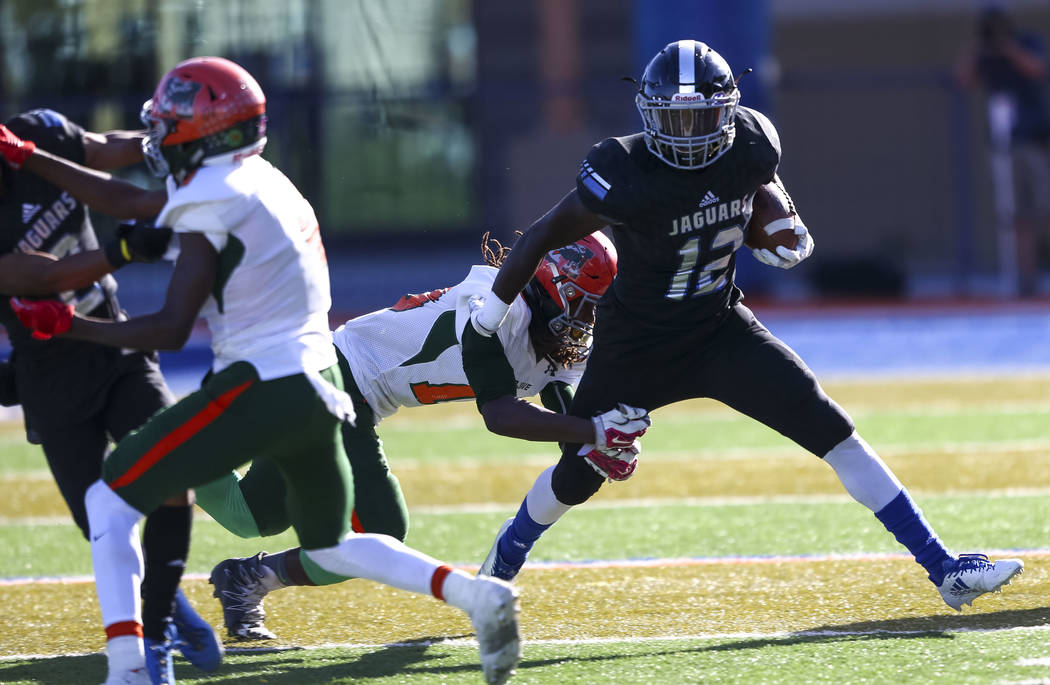 Desert Pines running back Jyden King (12) breaks a tackle while carrying the ball against Mojave in the NIAA Class 3A state championship game at Bishop Gorman High School in Las Vegas on Saturday, ...