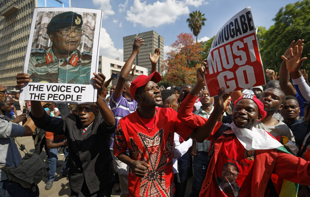 Protesters calling for the impeachment of President Robert Mugabe hold a placard of Zimbabwean Army General Constantino Chiwenga, left, as they demonstrate in front of the parliament building in d ...