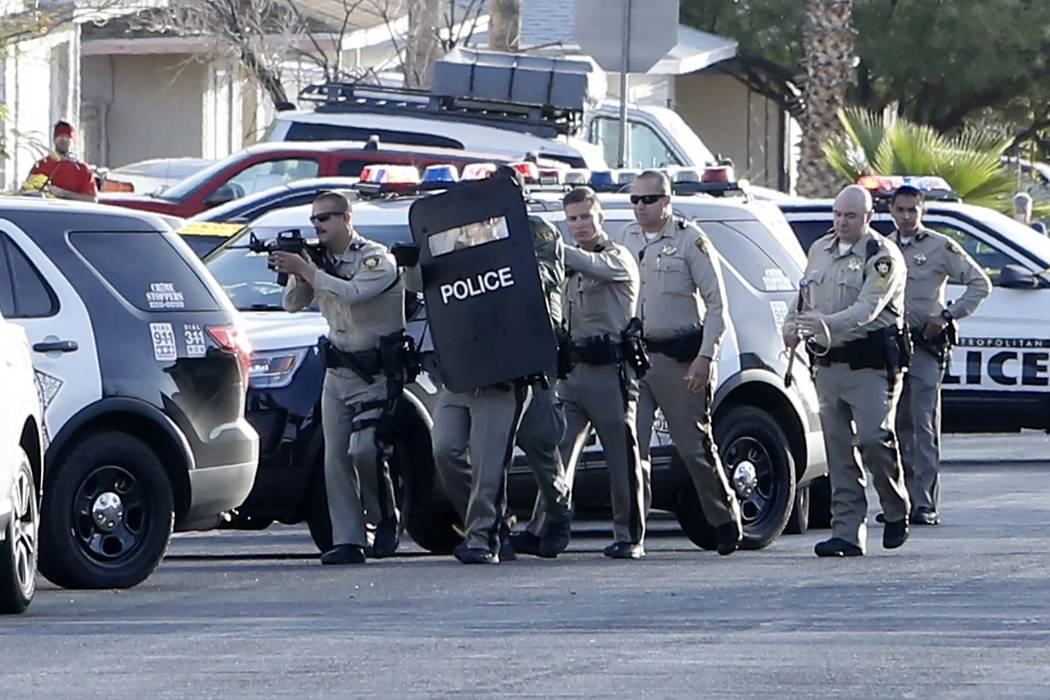 Metro officers shielded themselves behind a patrol car after reports of gunfire in the 7800 block of Genzer Drive, near Westcliff and Buffalo drives, Tuesday, Nov. 21, 2017, in Las Vegas. Officers ...