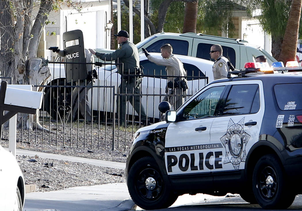 Metro officers approach the house where two people barricaded themselves in the 7800 block of Genzer Drive, near Westcliff and Buffalo drives, Tuesday, Nov. 21, 2017, in Las Vegas. Officers detain ...