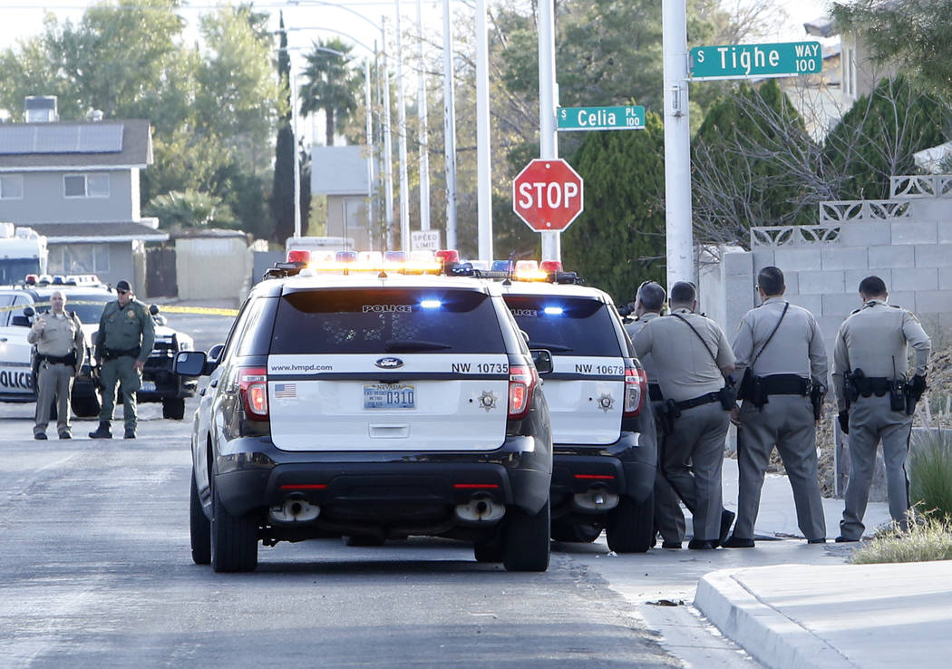 Metro officers shielded themselves behind a patrol car after reports of gunfire at the 7800 block of Genzer Drive, near Westcliff and Buffalo drives Tuesday, Nov. 21, 2017, in Las Vegas. (Bizuayeh ...