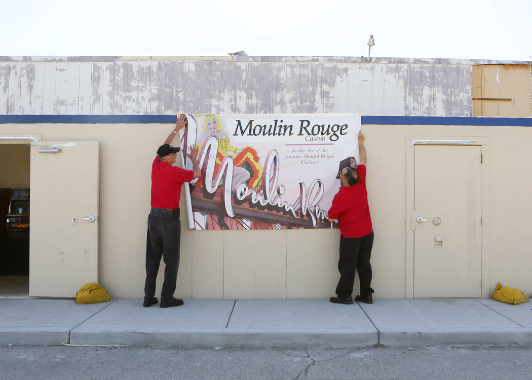 United Coin Machine Company employees Ben Blackford, left, and Joey Apicella hang a banner on a modular building containing slot machines at Moulin Rouge, located at 900 West Bonanza Rd., Wednesda ...