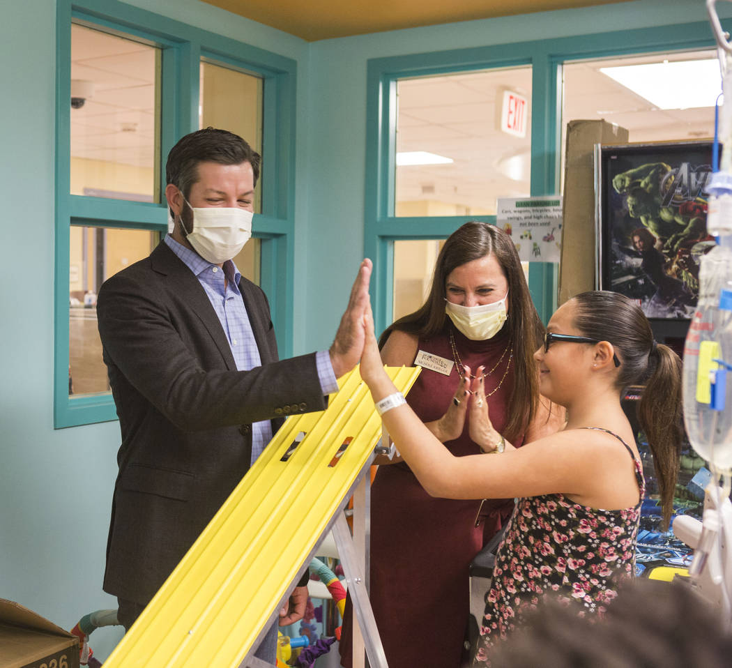 NASCAR champion Martin Truex, Jr. high fives a patient while the executive director for NASCAR Foundation Nichole Krieger claps after the raced toy race cars at Sunrise Children's Hospital in Las  ...