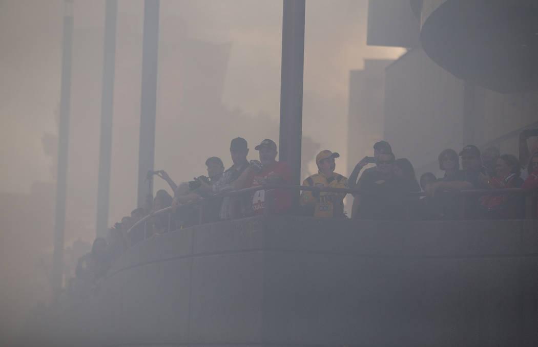 Race car fans watch through the smoke as drivers burn out on the Vegas Strip during Nascarճ Victory Lap on Wednesday, Nov. 29, 2017.  Richard Brian Las Vegas Review-Journal @vegasphotograph