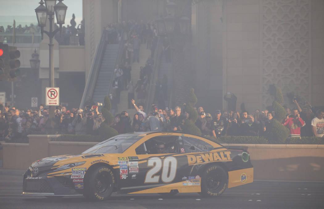 Race car driver Matt Kenseth (20) drives through a cloud of smoke on the Vegas Strip during NASCARճ Victory Lap on Wednesday, Nov. 29, 2017.  Richard Brian Las Vegas Review-Journal @vegaspho ...