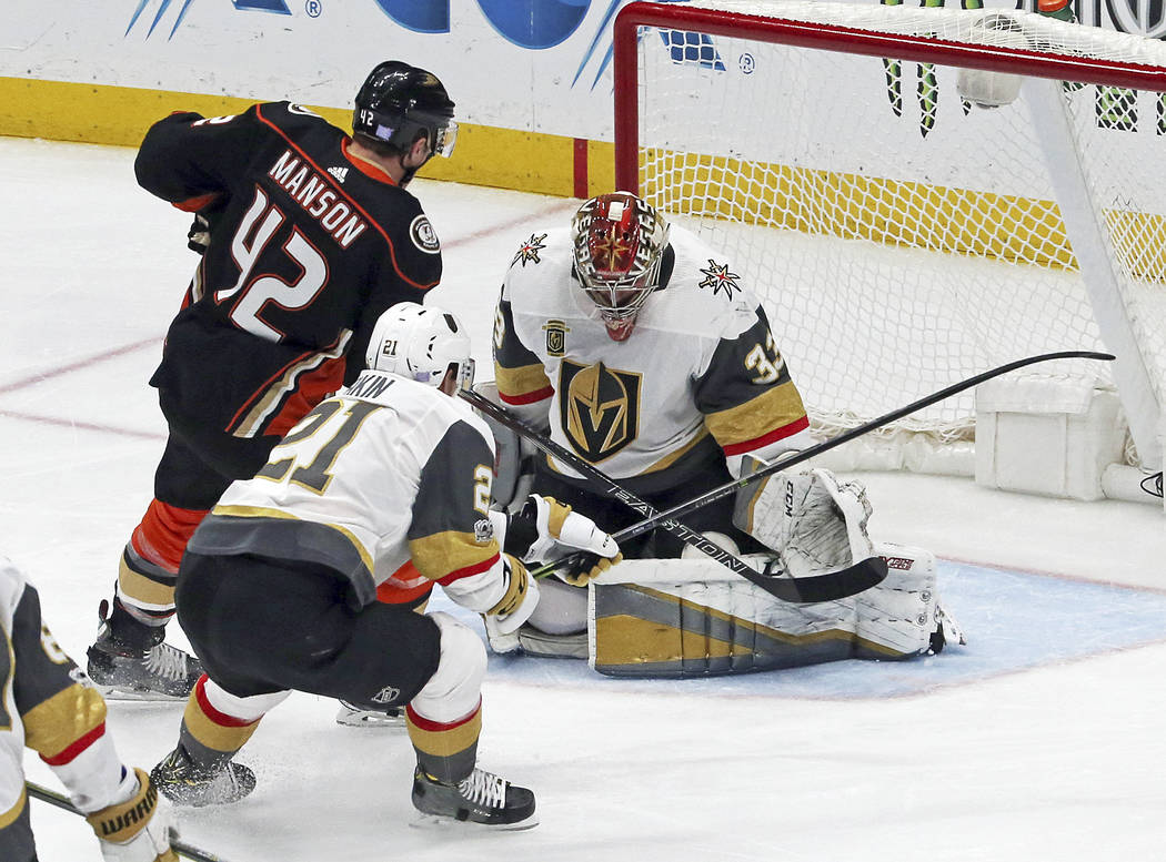 Anaheim Ducks defenseman Josh Manson (42) scores a goal on Vegas Golden Knights goalie Maxime Legace (33) and center Cody Eakin (21) in the first period of an NHL hockey game in Anaheim, Calif., W ...