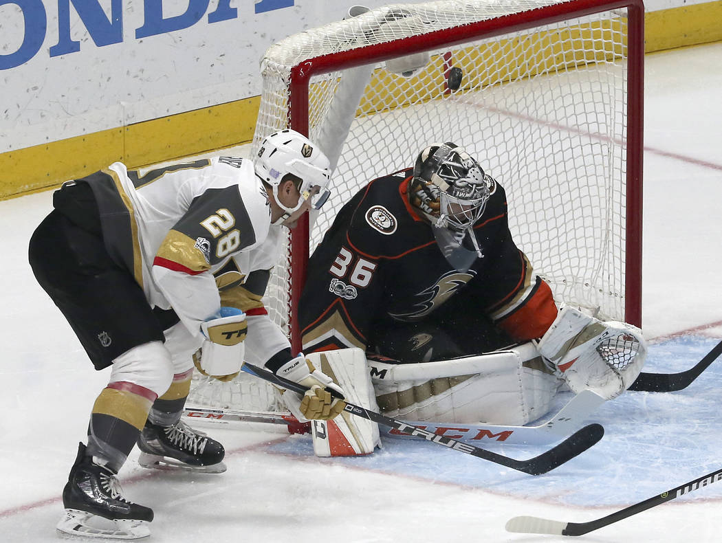 Anaheim Ducks goalie John Gibson (36) deflects the puck as Vegas Golden Knights left winger William Carrier (28) moves in in the first period of an NHL hockey game in Anaheim, Calif., Wednesday, N ...