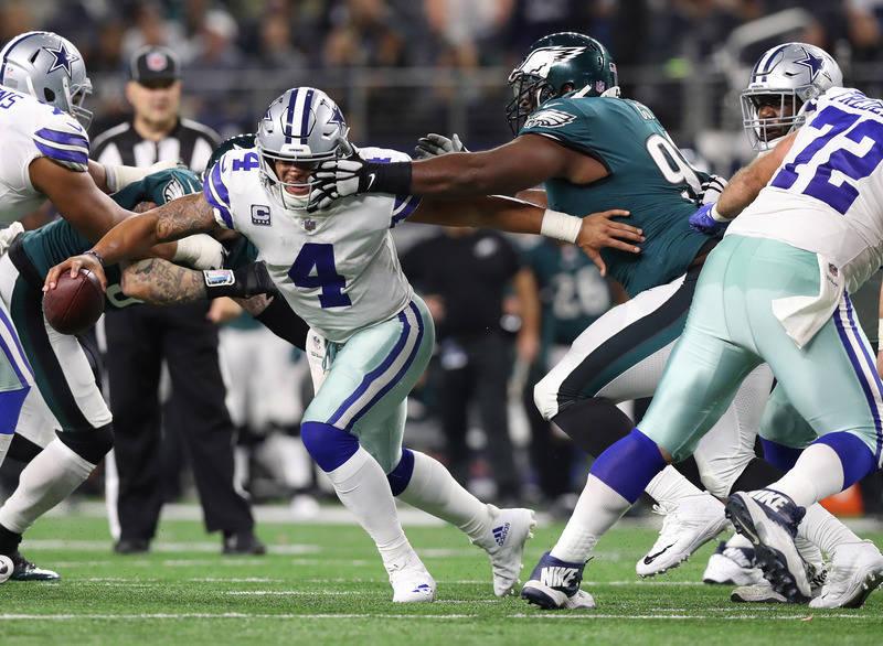 Nov 19, 2017; Arlington, TX, USA; Dallas Cowboys quarterback Dak Prescott (4) throws scrambles away from Philadelphia Eagles defensive tackle Fletcher Cox (91) in the fourth quarter at AT&T St ...