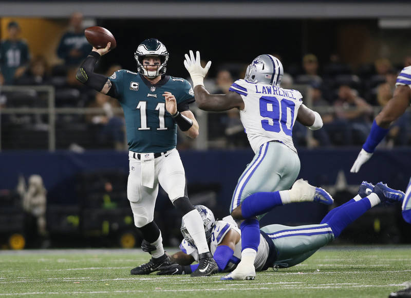Nov 19, 2017; Arlington, TX, USA; Philadelphia Eagles quarterback Carson Wentz (11) throws a pass against Dallas Cowboys defensive end DeMarcus Lawrence (90) in the fourth quarter at AT&T Stad ...