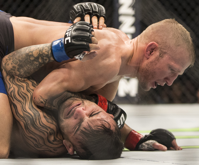 TJ Dillashaw works a submission against John Lineker during their bantamweight fight at UFC 207 at T-Mobile Arena on Friday, Dec. 30, 2016, in Las Vegas. Benjamin Hager/Las Vegas Review-Journal