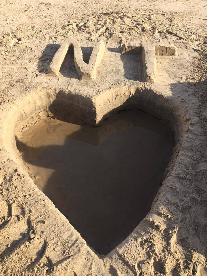 A heart carved out of sand is seen with Neysa Tonks' initials on top at Newport Beach in Calif., Nov. 20, 2017. (Smith Family).