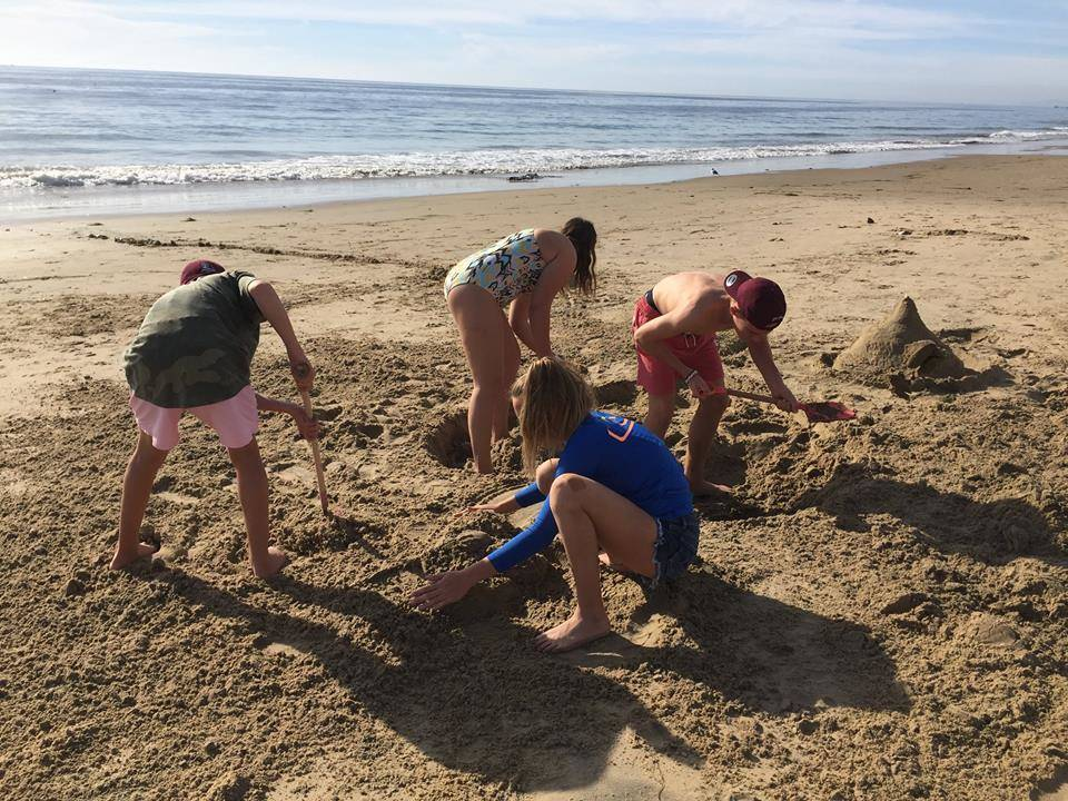 Greysen Tonks, 14, clockwise from top left, Lexy Smith, Braxton Tonks, 17 and Kenzy Smith carved a heart out of sand with Neysa Tonks' initials in her honor at Newport Beach in Calif., Nov. 20, 20 ...