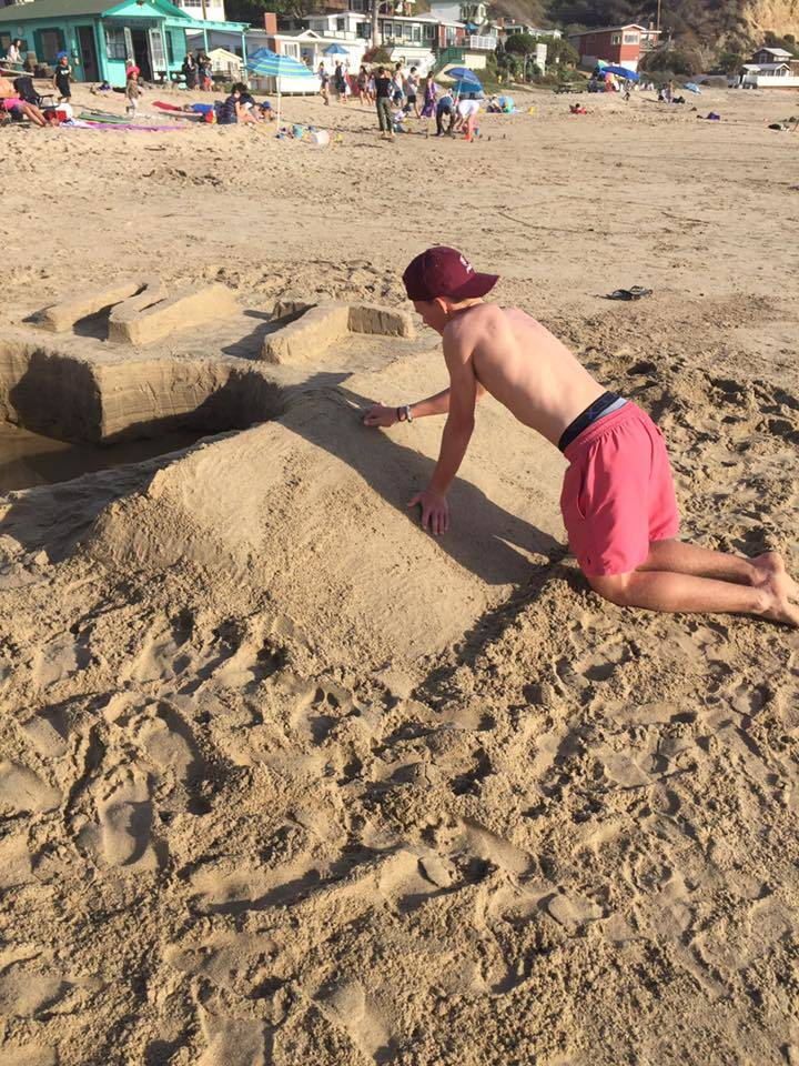 Braxton Tonks, 17, works on creating a sand monument in memory of his mother, Nesya Tonks, at Newport Beach in Calif., Nov. 20, 2017. (Smith Family).