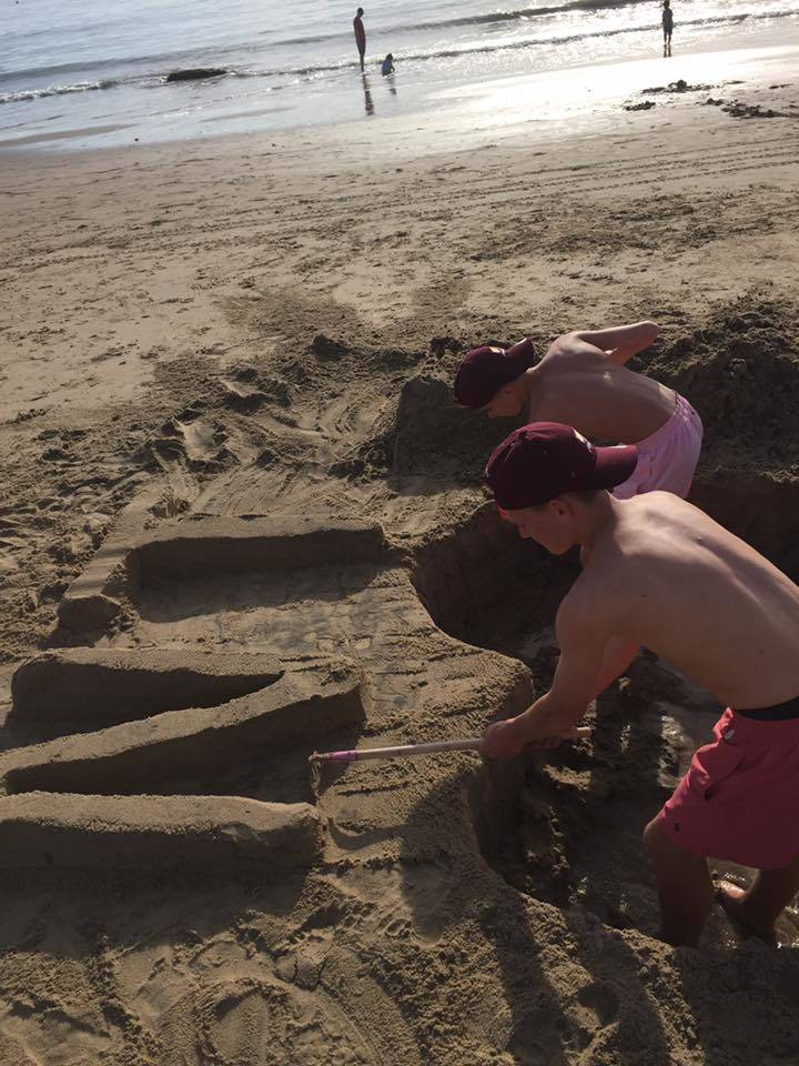 Braxton Tonks, 17, and his brother Greysen, 14, work on creating a sand monument in memory of their mother, Nesya Tonks, at Newport Beach in Calif., Nov. 20, 2017. (Smith Family).