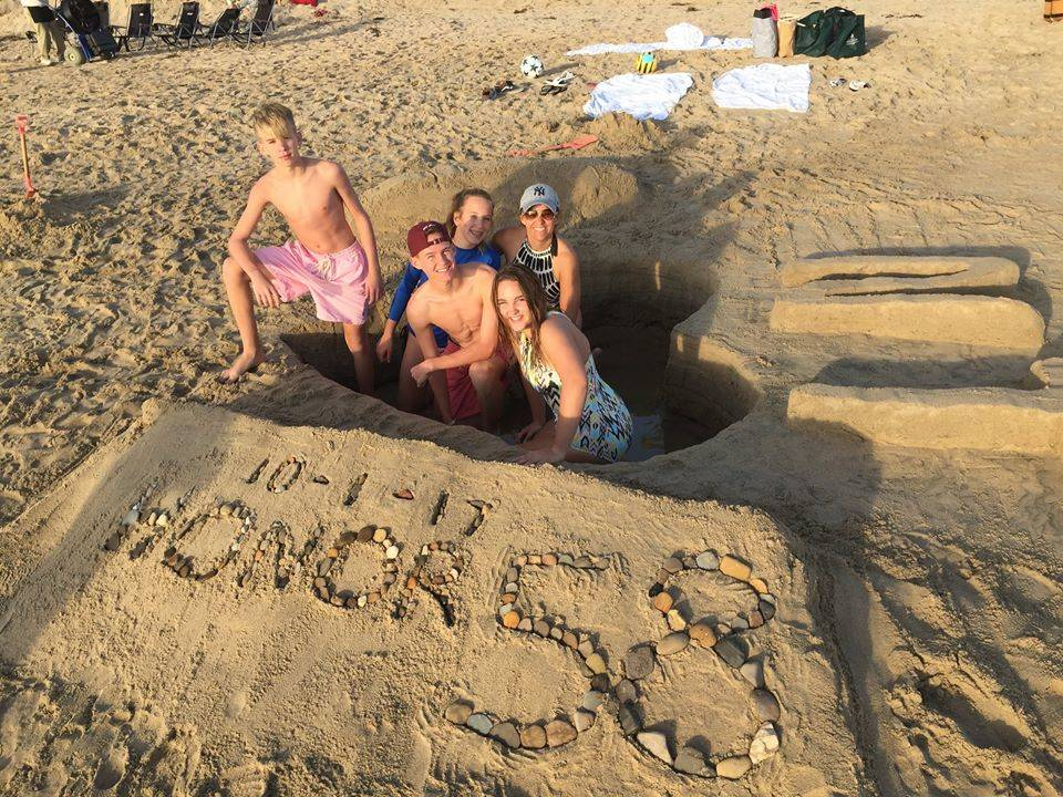 Greysen Tonks, 14, clockwise from top left, Braxton Tonks, 17, Kenzy Smith, Mynda Smith and Lexy Smith stand inside a heart carved out of sand in honor of Nesya Tonks at Newport Beach in Calif., N ...