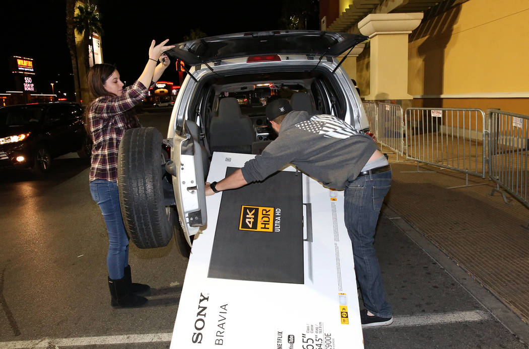 Brandon Pritchard and his wife, Britney, load their flatscreen TV into the trunk of an SUV after Thanksgiving Day shopping at Best Buy in Henderson Friday, Nov. 24, 2017, in Las Vegas. Bizuayehu T ...