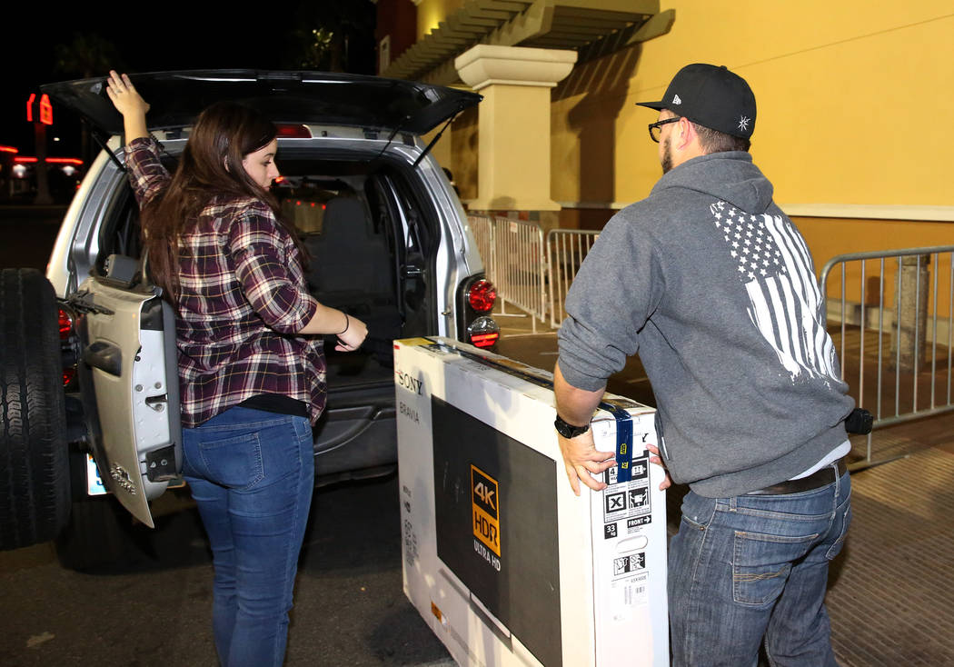 Brandon Pritchard and his wife Britney load their flat screen TV into the trunk of an SUV after Thanksgiving Day shopping at Best Buy in Henderson Friday, Nov. 24, 2017, in Las Vegas. Bizuayehu Te ...