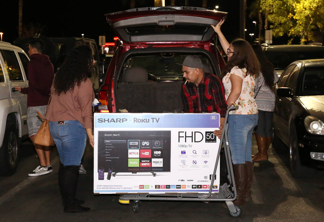 Daniel Lopez, center, loads his flat screen TV into the trunk of an SUV after Thanksgiving Day shopping at Best Buy in Henderson Friday, Nov. 24, 2017, in Las Vegas. Bizuayehu Tesfaye Las Vegas Re ...