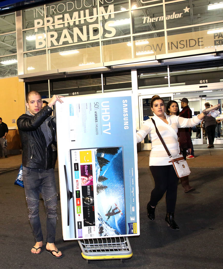 Louis Tamarit, left, and Luisa Puentes walk out with their flat screen TV purchase after Thanksgiving Day shopping at Best Buy in Henderson Friday, Nov. 24, 2017, in Las Vegas. Bizuayehu Tesfaye L ...