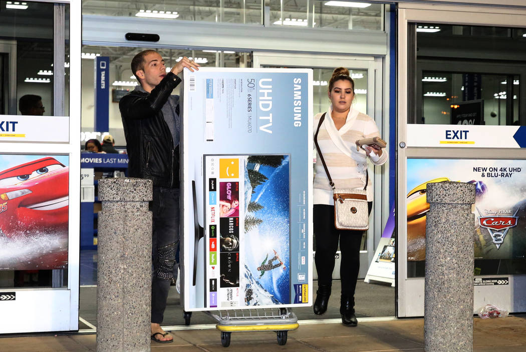 Louis Tamarit, left, and Luisa Puentes walk out with their flatscreen TV purchase after Thanksgiving Day shopping at Best Buy in Henderson Friday, Nov. 24, 2017, in Las Vegas. Bizuayehu Tesfaye La ...