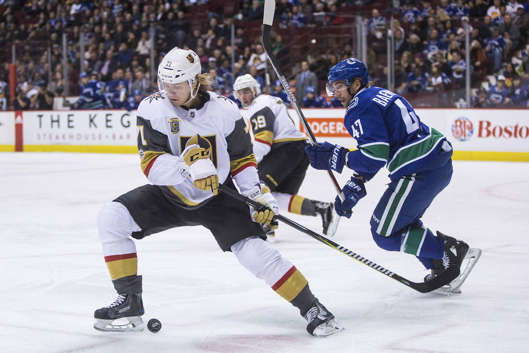 Vegas Golden Knights' William Karlsson (71), of Sweden, controls the puck in front of Vancouver Canucks' Sven Baertschi (47), of Switzerland, during the first period of an NHL hockey game Thursday ...