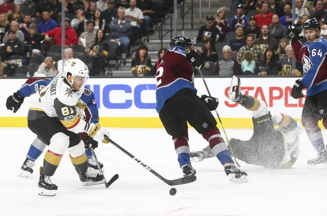 Golden Knights' James Neal (18), right, gets tripped up as Golden Knights' Jonathan Marchessault (81) moves the puck against the Colorado Avalanche during an NHL hockey game at T-Mobile Arena in L ...