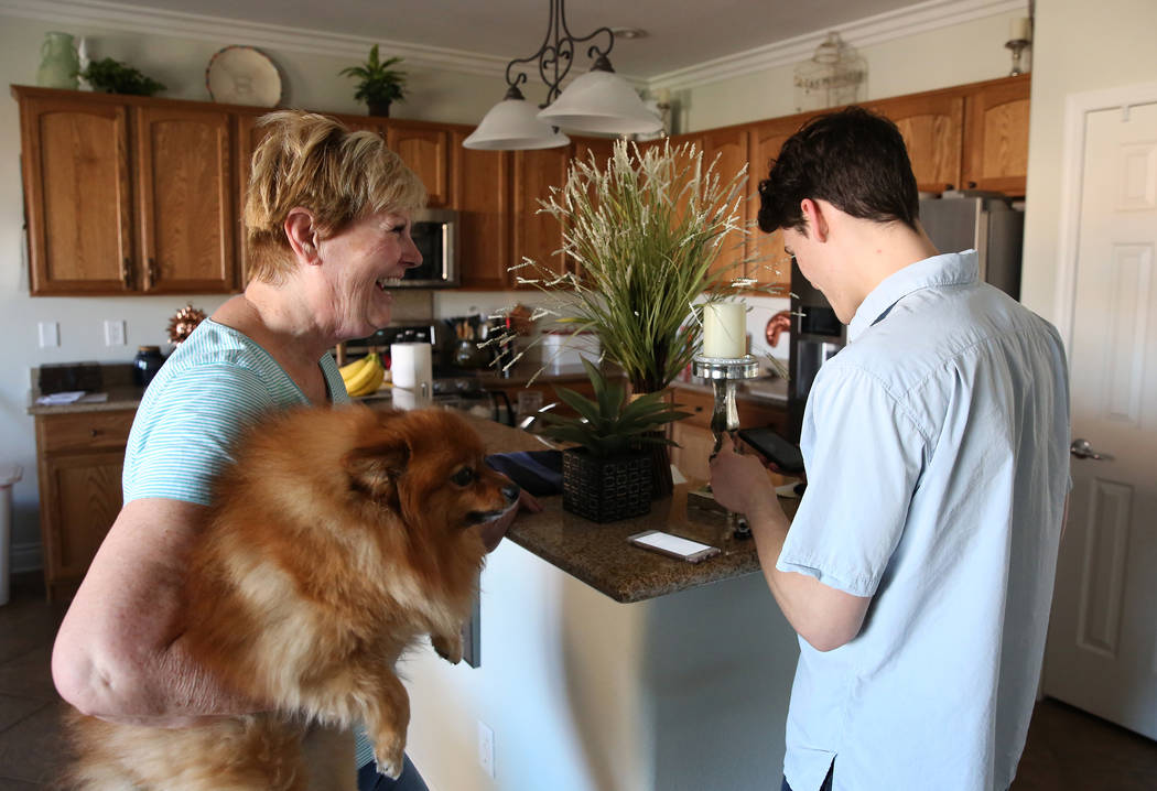 Kai Otterson and her dog Jackson watch as Hudson Root sets up her earbuds at her Henderson home on Wednesday, Nov. 22, 2017. Root started a community service project called Geeks for Seniors as a  ...
