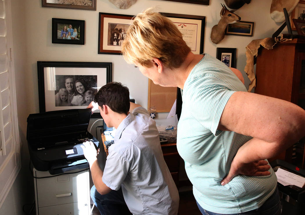 Kai Otterson watches as Hudson Root sets up her new wireless printer at her Henderson home on Wednesday, Nov. 22, 2017. Root started a community service project called Geeks for Seniors as a way t ...