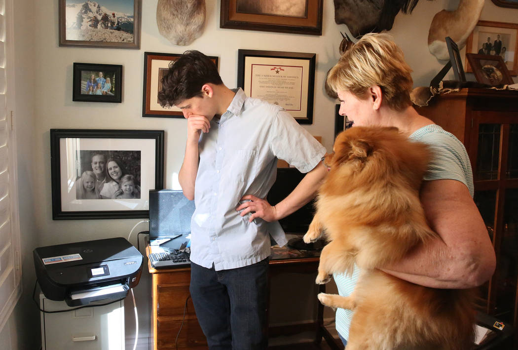 Kai Otterson and her dog Jackson, right, watch as Hudson Root tries to set up her new wireless printer at her Henderson home on Wednesday, Nov. 22, 2017. Root started a community service project c ...