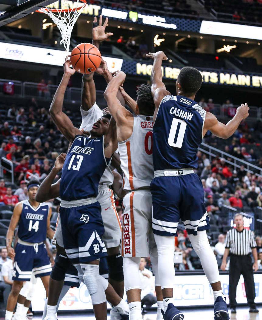 Rice Owls forward Malik Osborne (13), left, jumps for a rebound during the first half of basketball game against the UNLV Rebels during day one of the MGM Grand Main Event tournament at T-Mobile A ...