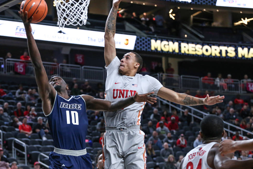 Rice Owls forward Robert Martin (10), left, shoots the ball as he is guarded by UNLV Rebels forward Anthony Smith (2), right, during the second half of basketball game during day one of the MGM Gr ...