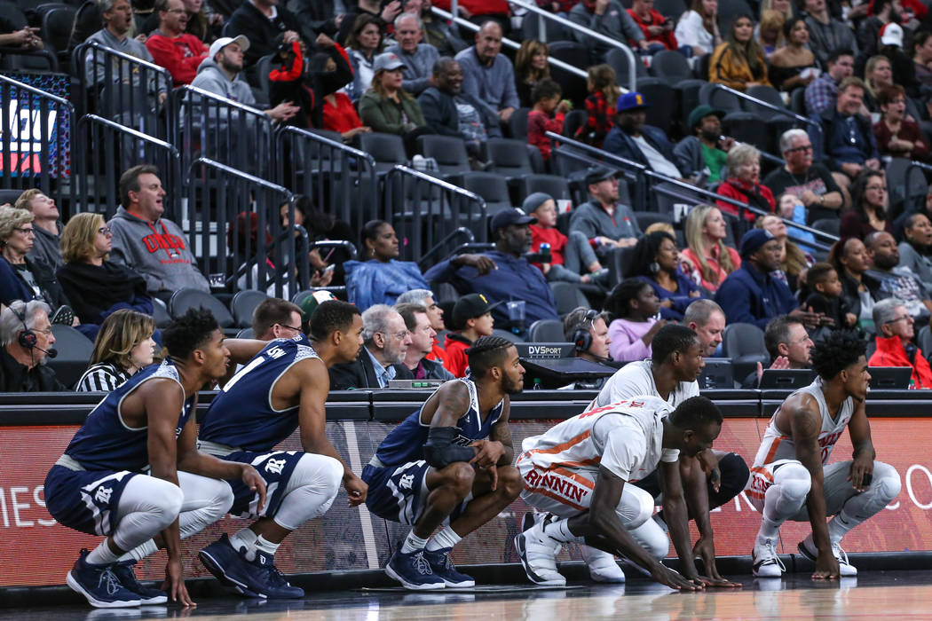 Players from the Rice Owls, left, and the UNLV Rebels, right, wait to be subbed in during the second half of basketball game during day one of the MGM Grand Main Event tournament at T-Mobile Arena ...