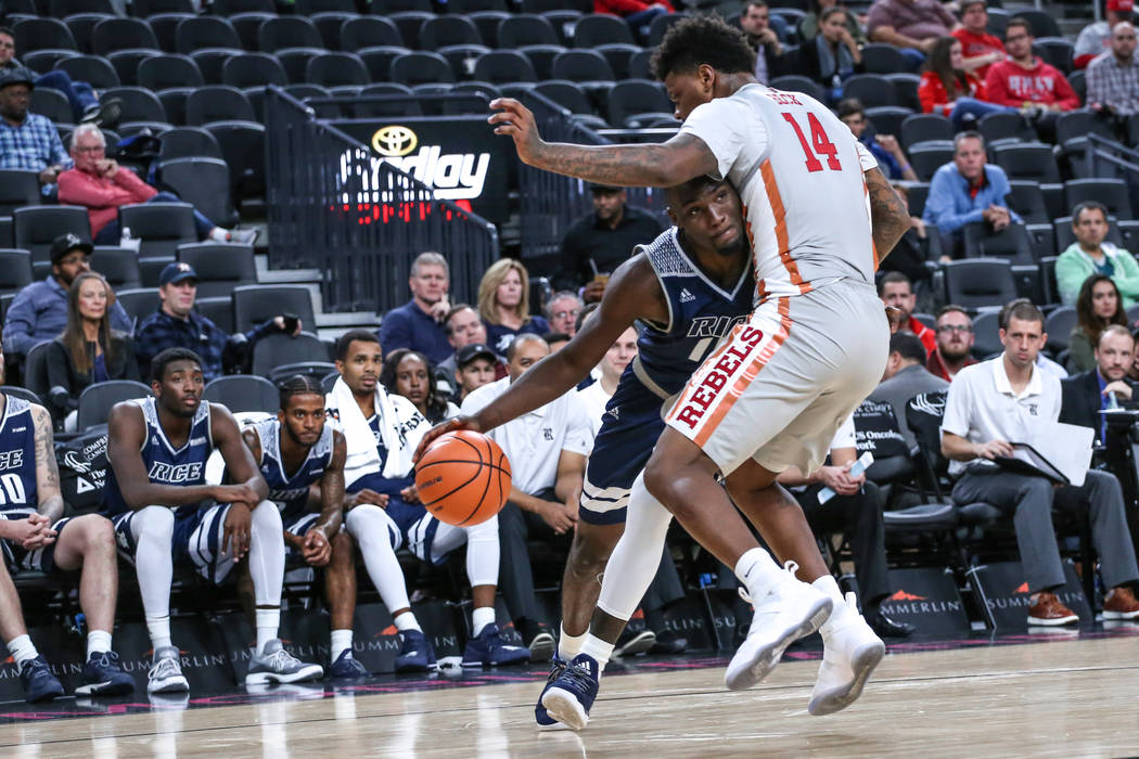 Rice Owls forward Robert Martin (10), left, is guarded by UNLV Rebels forward Tervell Beck (14), right, during the second half of basketball game during day one of the MGM Grand Main Event tournam ...