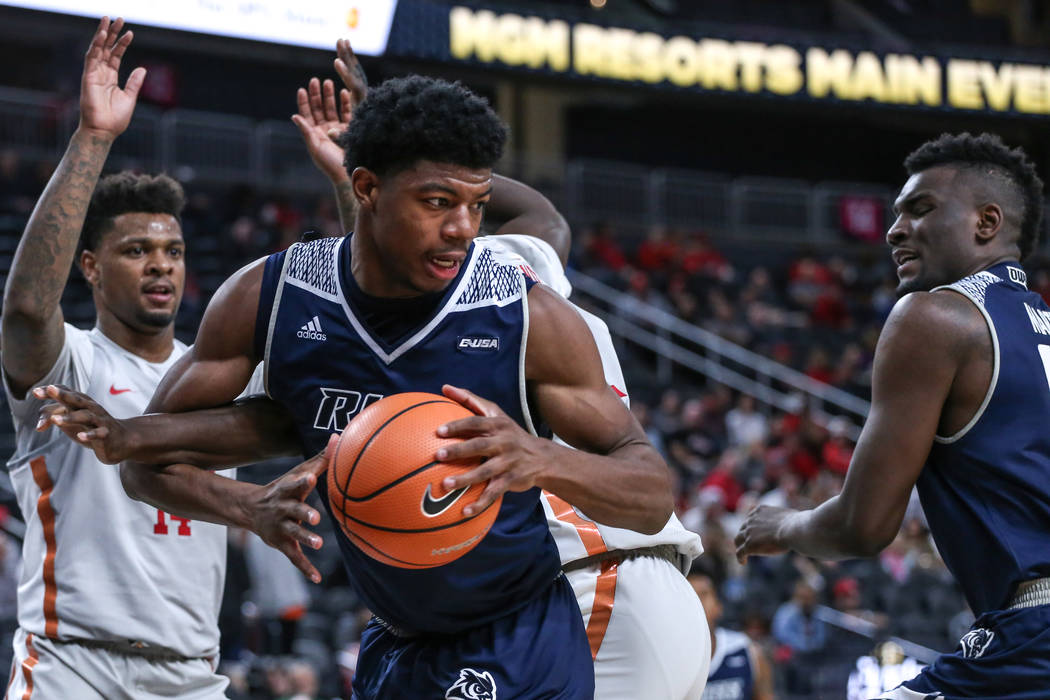Rice Owls forward Malik Osborne (13) holds the ball as he is guarded by the UNLV Rebels during the second half of basketball game during day one of the MGM Grand Main Event tournament at T-Mobile  ...