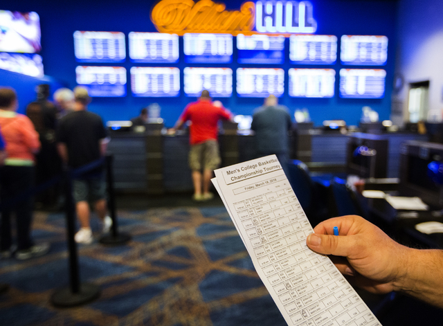Wes Dorner from Green Bay, Wis. checks a parlay card for the NCAA Men's basketball in the William Hill Race & Sports Book at the Plaza Hotel-Casino on Friday, March 18, 2016. Jeff Scheid/Las V ...