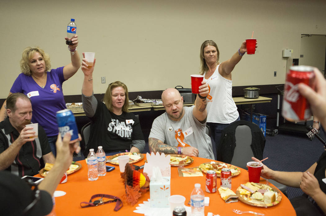 Survivors raise there glass for a toast during a Thanksgiving dinner for Route 91 Harvest festival survivors at the Henderson Convention Center in Henderson, Saturday, Nov. 25, 2017. Bridget Benne ...