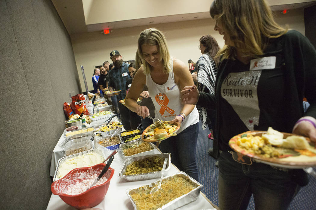 One of the event organizers Shawna Bartlett, center, grabs food during a Thanksgiving dinner for Route 91 Harvest festival survivors at the Henderson Convention Center in Henderson, Saturday, Nov. ...