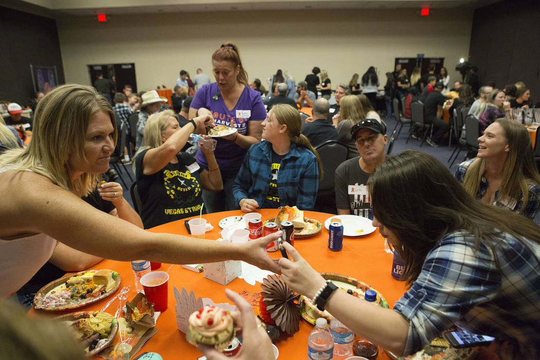 One of the dinner's organizers Shawna Bartlett, left, shares a photo of the concert with Alicia Gomez, right, during a Thanksgiving dinner for Route 91 Harvest festival survivors at the Henderson  ...