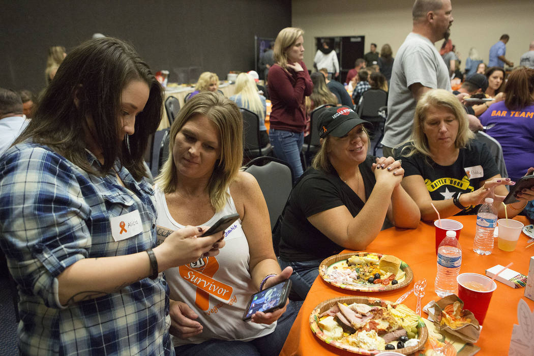 One of the dinner's organizers Shawna Bartlett, right, and  Alicia Gomez, left, share a photos of the concert during a Thanksgiving dinner for Route 91 Harvest festival survivors at the Henderson  ...