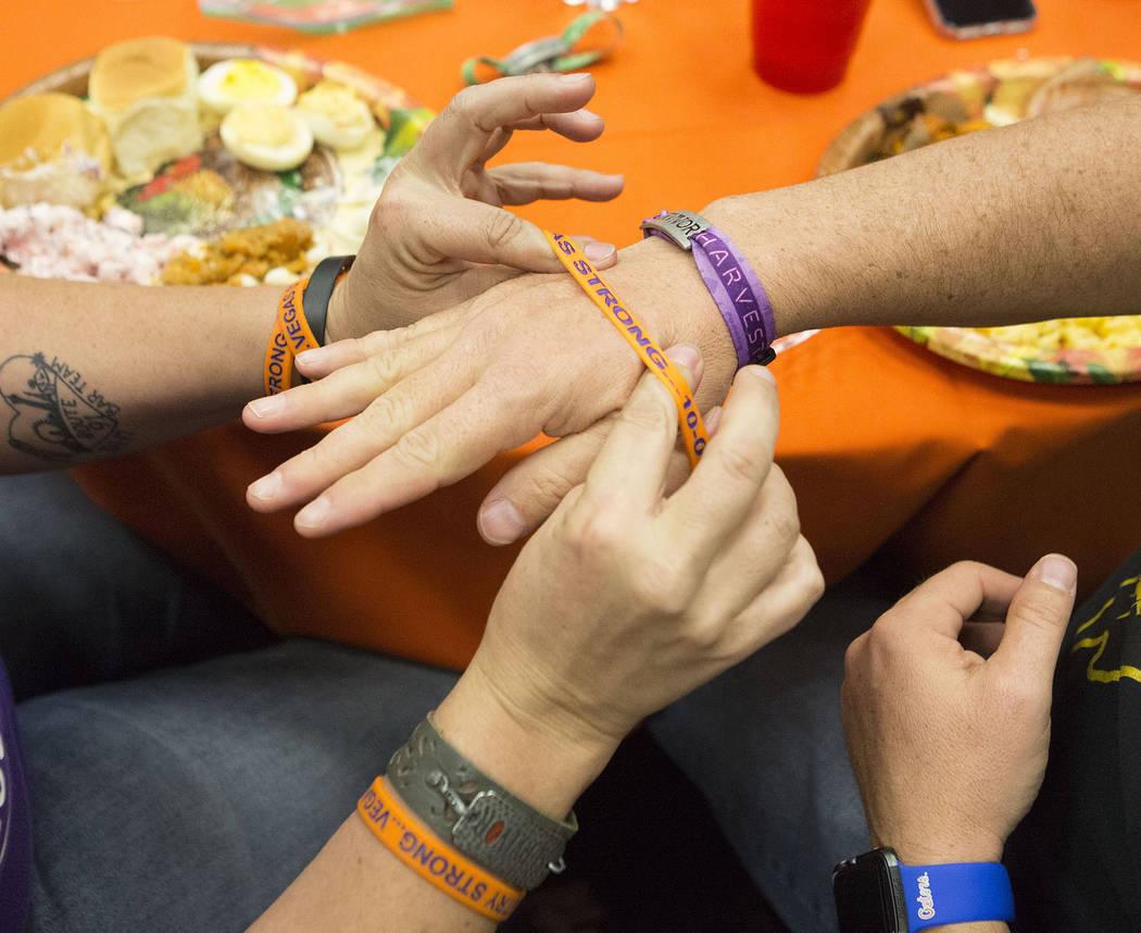 "Heather Goose, left, gives Steve York a ""Vegas Strong"" bracelet during a Thanksgiving dinner for Route 91 Harvest festival survivors at the Henderson Convention Center in Henders ..."